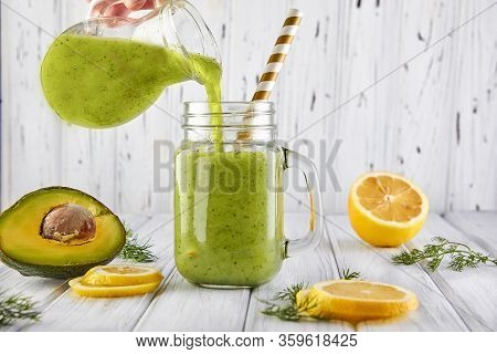 A Healthy Green Smoothie Is Poured From A Jug Into A Jar. Green Smoothie With Organic Ingredients, V