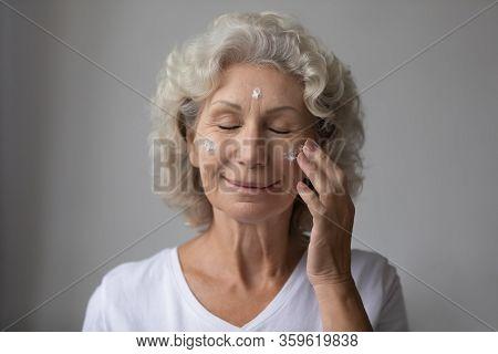 Smiling Beautiful Middle Aged Senior Retired Woman Nourishing Moisturizing Face.