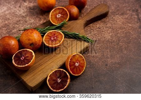 Copy Space With Sliced Sicilian Blood Oranges Fruits On Cut Board With Rosemary Branch On Rusty Back
