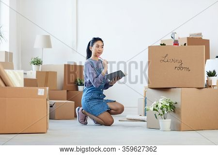Full Length Portrait Of Young Asian Woman Organizing Moving In Process While Sitting On Floor Next T