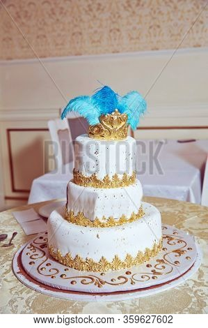 The Cake Has Blue Feathers And A Golden Crown . White Three-tiered Cake.