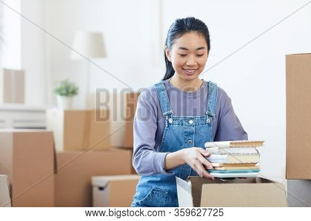 Portrait Of Young Asian Woman Packing Books To Cardboard Boxes And Smiling Happily Excited For Movin