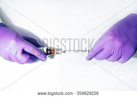 Doctor In White Coat And Purple Gloves Prepares A Vaccine Or Medicine In A Syringe. Medicine And Hea