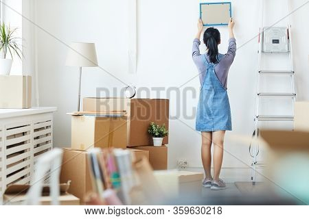 Full Length Back View Portrait Of Young Asian Woman Decorating New Home While Moving In To New House