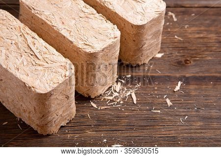 Pressed Sawdust Fuel Briquettes. Briquettes For The Oven Close-up. Set Of Fuel Briquettes On A Woode