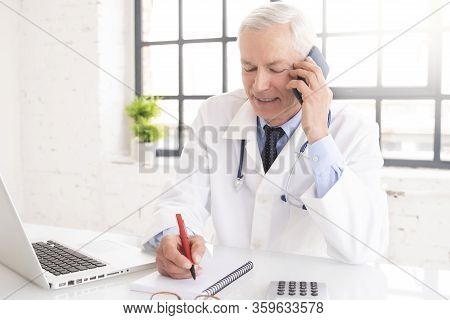 Senior Male Doctor Using Mobile Phone And Laptop While Working In Doctor's Office
