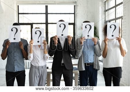 Business People Hiding Faces Behind Papers Sheets With Question Marks.