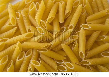 Penne Pasta Background. Pasta Penne Texture Background. Tube Like Macaroni. Heap Of Pasta. Top View.