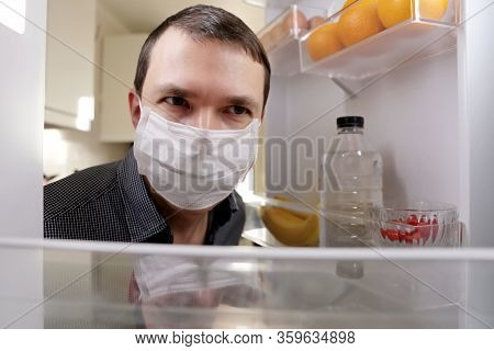 Man In A Medical Mask Looks Into The Fridge With Food. Concept Of Diet, Obesity During Home Quaranti