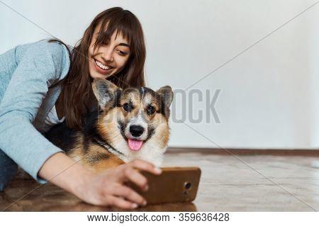 Joyful Smiling Young Woman Hugging Cute Welsh Corgi Dog Dog And Taking Selfie With Pet On Smartphone