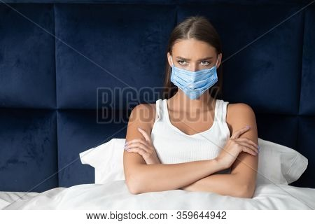 Coronavirus Quarantine. Bored Girl In Medical Mask Sitting Crossing Hands In Bed Suffering From Bori