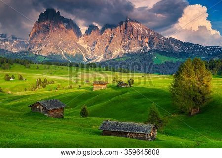 Gorgeous Summer Alpine Place With Wooden Lodges And Snowy Mountains At Sunset, Dolomites, Alpe Di Si