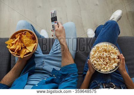 Top View Close Up Of Unrecognizable Couple Watching Tv Together While Sitting On Cozy Sofa At Home A
