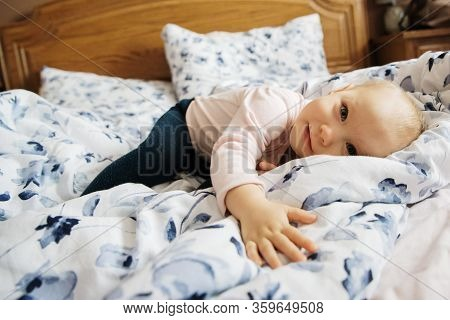 Baby Girl In The Parents Bed Smiling