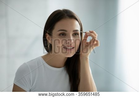 Young Woman Look In Mirror Pinching Eyebrows With Tweezers