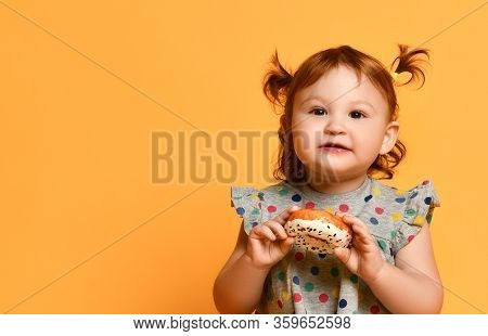 Funny Toddler Girl With Two Ponytails, In Gray Polka Dot Dress And White Sandals. She Sitting On Flo