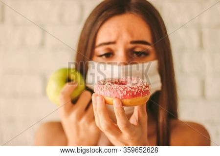 Sports Woman In Protective Mask On Face Deciding Between Healthy Food Or Sugar Snack. Fitness Girl I