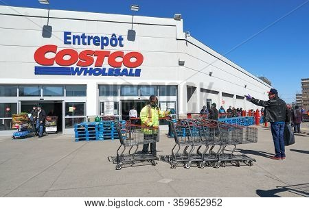 Montreal, Canada - April 4. 2020: People With Masks In A Line To Enter Costco Wholesale. Many Stores