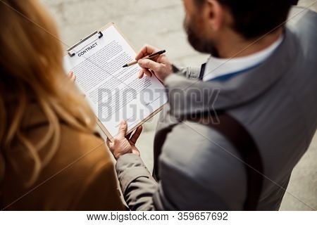 Buyer And A Realtor Reading Through A Document