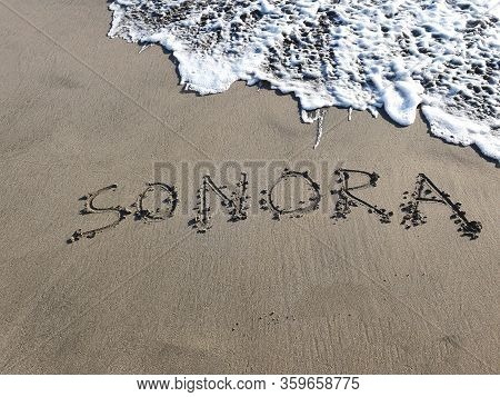 Sonora Text Handwritten In Beach Sand, Background And Texture