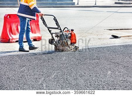 A Road Worker Compacts Asphalt In A Fenced Section Of The Road On The Carriageway Using A Gasoline V