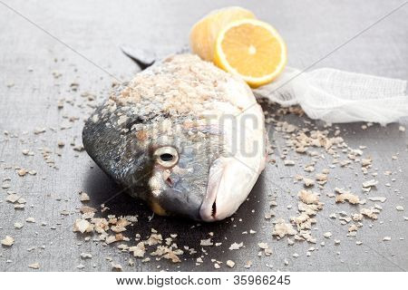 Fresh gilt head bream with sea salt crystals and lemon on shiny silver background. Luxurious seafood concept. poster