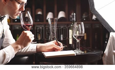 Sommelier Holds A Glass Of Wine, Looks At The Glass Of Wine And Tastes The Aroma Of Wine In The Glas