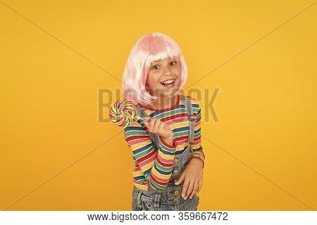 Her Favorite Rainbow Swirl Dessert On Stick. Small Child Enjoy Hard Candy Dessert Yellow Background.