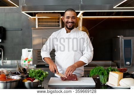 Handsome Young African Chef Standing In Professional Kitchen In Restaurant Preparing A Meal Of Meat