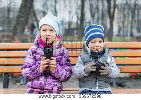 Two Cute Adorable Siblings Children Sitting On Wooden Bench And Drinking Hot Chocolate, Tea Or Cocoa
