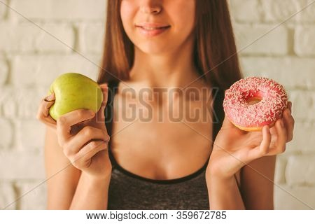 Closeup Young Sexy Fitness Girl Holding Apple And Donut In Hands. Beautiful Slim Sports Woman Choosi