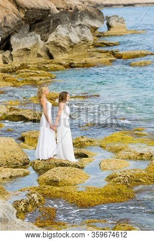 Beautiful And Pretty Ladies, Mother And Daughter Stands In White Long Dress At Cyprus Rocky Coast, N