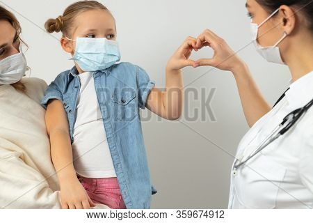 Caucasian Mother And Her Kid Wearing Medical Masks In Clinic