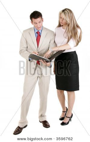 Businesswoman And Businessman Reviewing Notes.