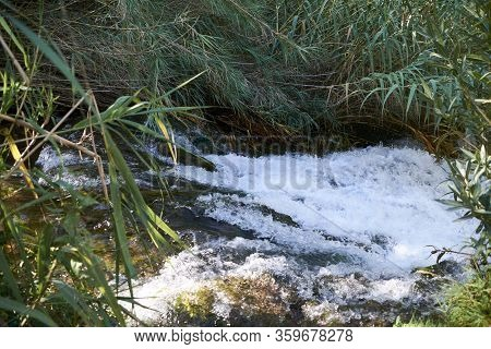 River Of Turbulent Waters In A Small Waterfall, Long Exposure, Vegetation, Transparent