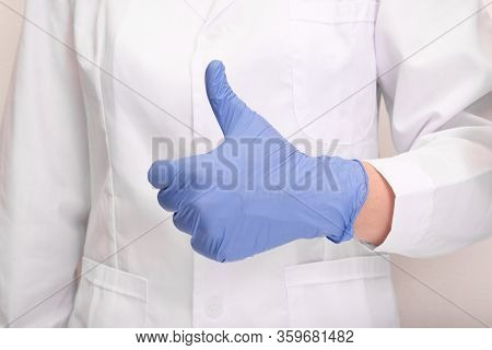 A Doctor In Uniform And Blue Nitrile Gloves Showing Thumb Up.