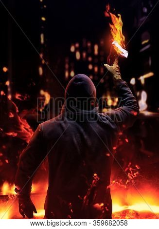 Photo of a protester in mask and hood holding and raising up burning molotov cocktail on night streets city background.