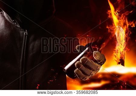 Photo of a protester in mask and hood holding burning molotov cocktail close-up view on dark fire background.