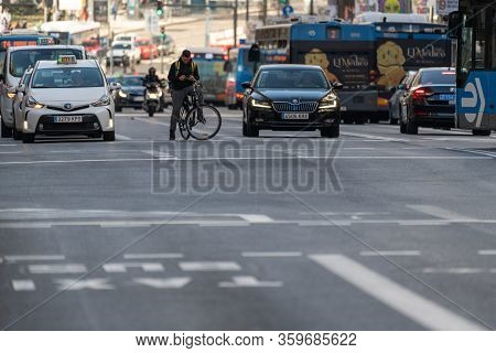 Madrid, Spain - February 24, 2019: City Buses, Cars, Bicycles And Motorbikes Are Waiting At A Traffi