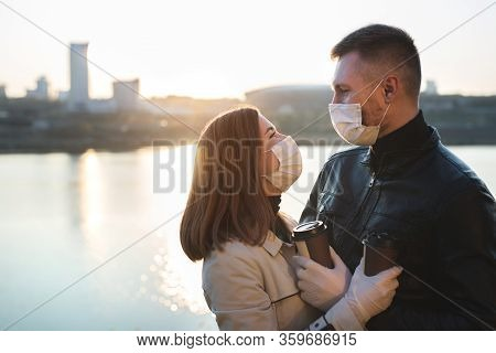 Young Couple, A Man And A Woman In Medical Masks And Gloves, Drink Coffee From Disposable Cups On Th