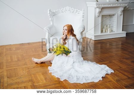 Portrait Of A Red-haired Beautiful Girl With A Mimosa In A Long White Dress