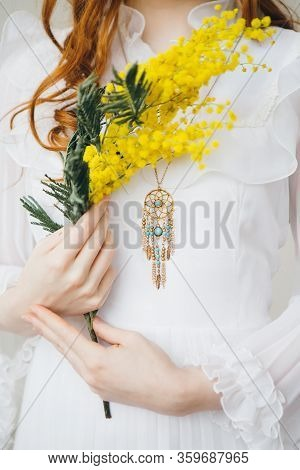 Portrait Of A Red-haired Beautiful Girl With A Mimosa In A Long White Dress. Spring Concert. Toning.