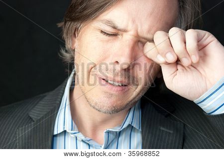 Stressed Businessman Rubs Eyes