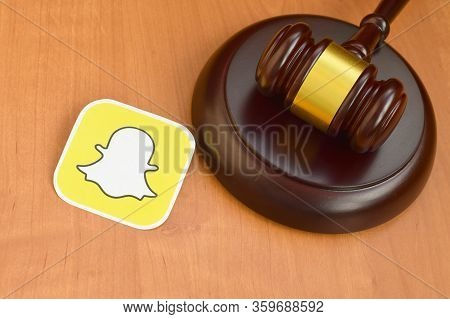 Snapchat Paper Logo Lies With Wooden Judge Gavel. Entertainment Lawsuit Concept