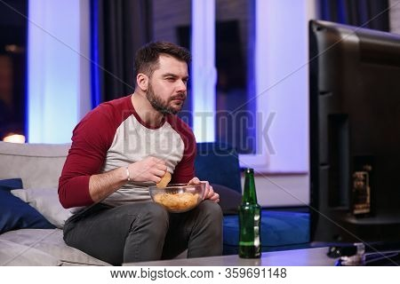 Good-looking Modern Positive 30-aged Guy With Well-groomed Beard Savoring Chipps During Emotional Re