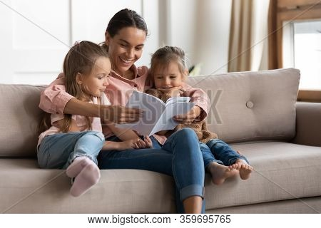 Happy Young Mixed Race Babysitter Reading Book To Children.