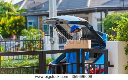 Asian Young Delivery Man Courier Online With Box In Blue Cap And T-shirt Uniform He Protective Face