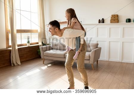 Happy Father Giving Piggyback Ride To Overjoyed Little Daughter.