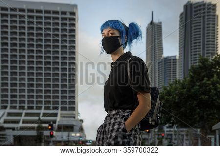 Young Female Wearing Medical Mask In Modern City Street, Stylish Trendy Girl With Blue Hair Wearing