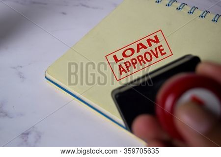 Red Handle Rubber Stamper And Loan Aprroved Text Isolated On White Background.